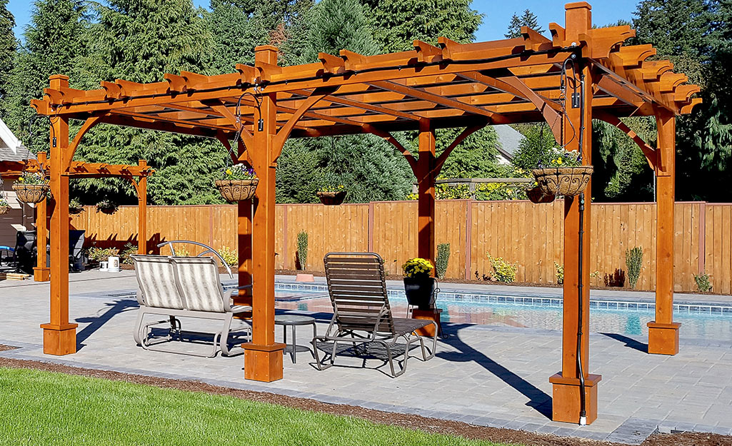 A pergola with chairs by a pool.