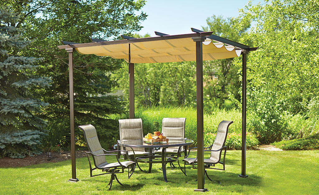 A pergola and patio furniture set up in the garden.