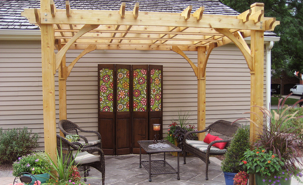 Pergola on a backyard patio with outdoor furniture.