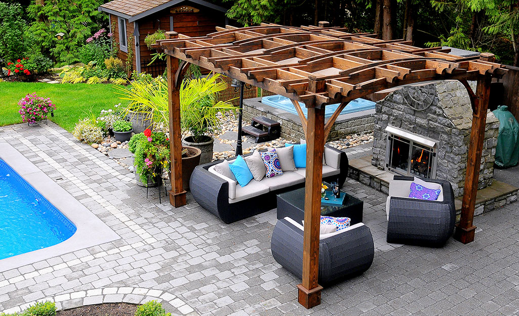 Pergola with patio furniture beside a pool.