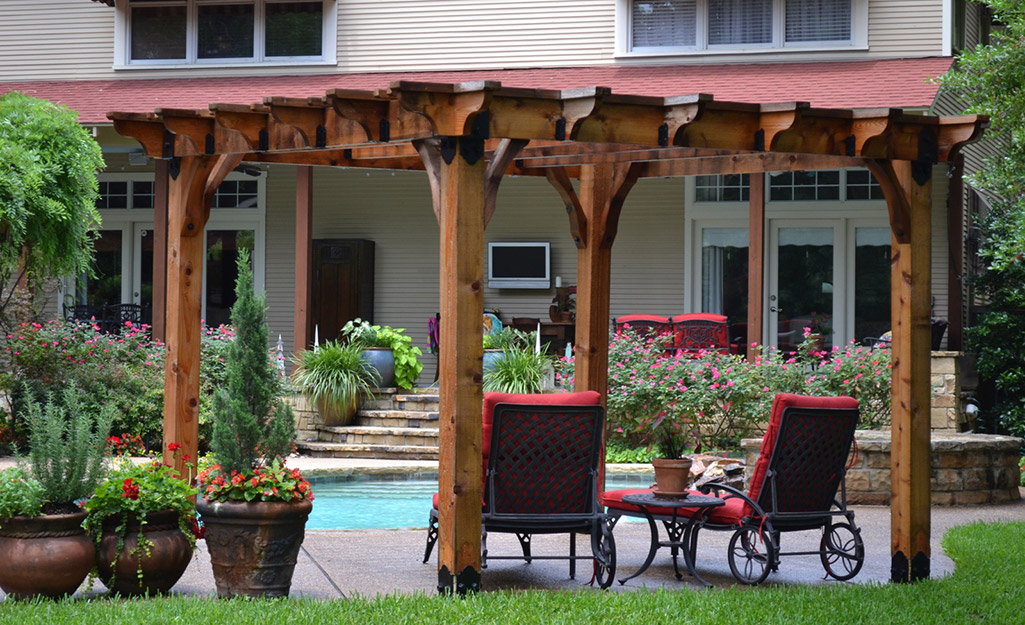 Pergola poolside with plants.
