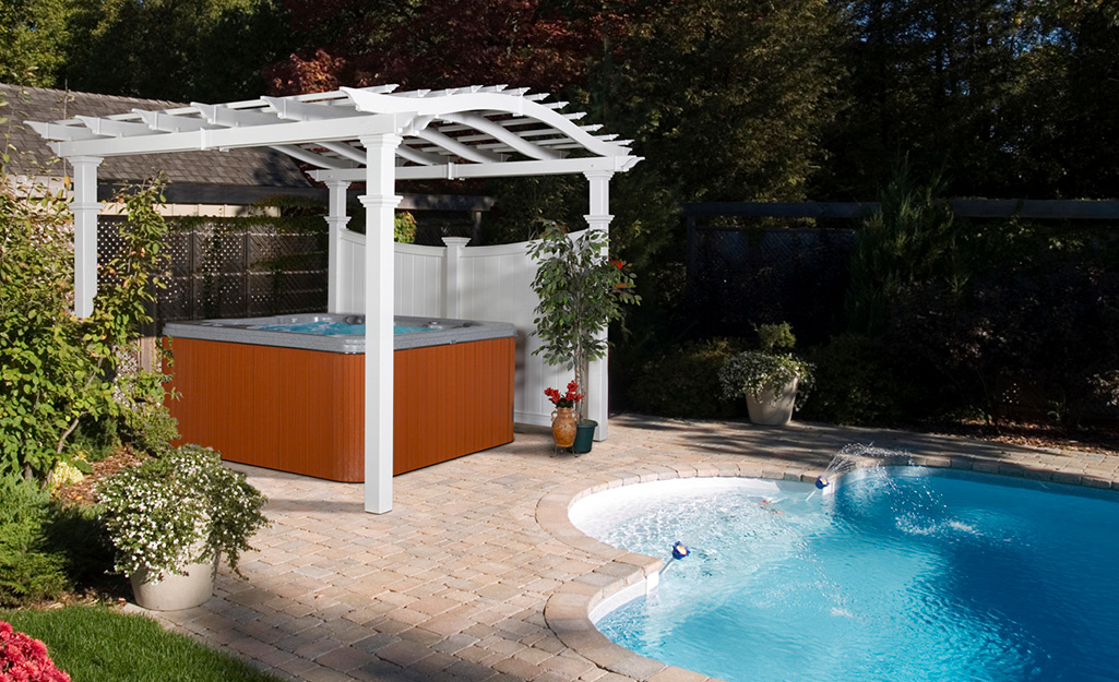 A pergola protects the hot tub from the sun.