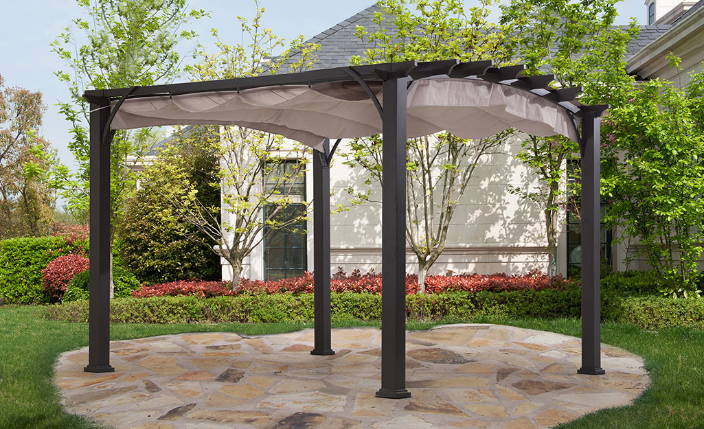 Pergola with adjustable canopy in the garden.