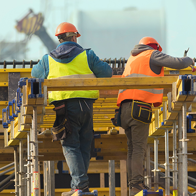 two construction workers on a job site wearing PPE