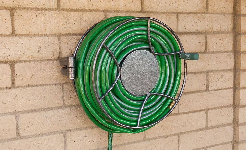 A garden hose reel mounted to a brick wall.