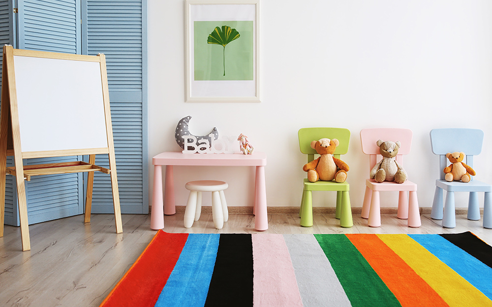 Một phòng chơi với một tấm thảm đầy màu sắc trên sàn.