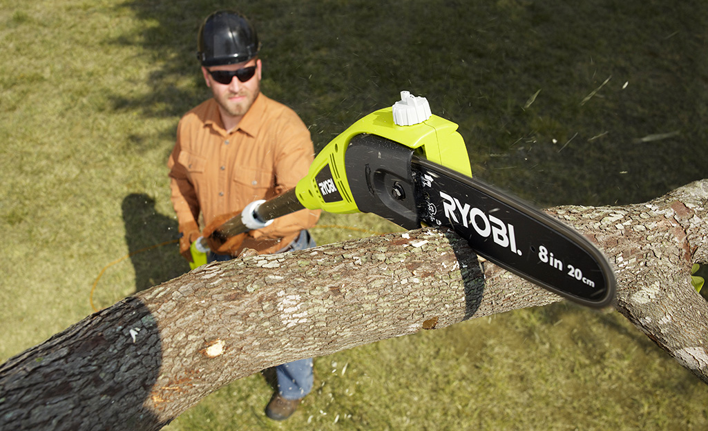 A man uses an electric pole saw to cut a branch.