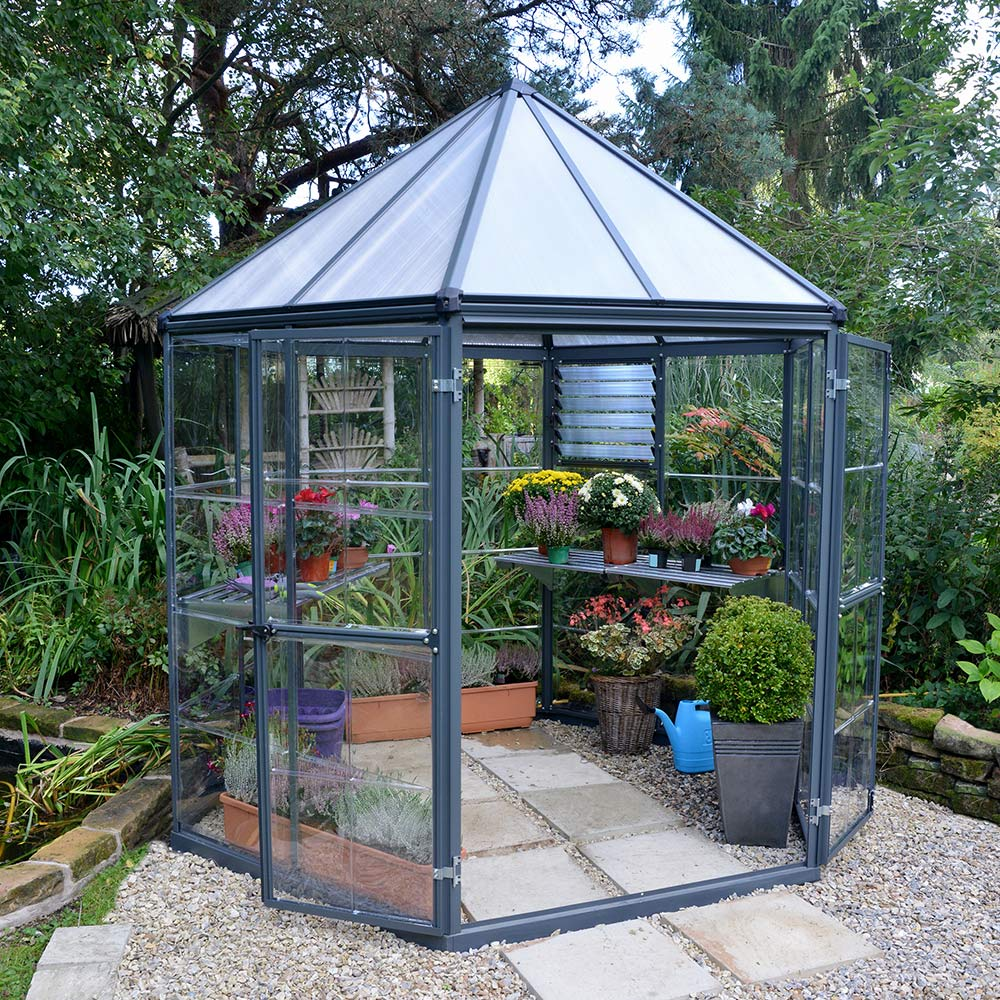 A small greenhouse with a peaked polycarbonate roof.