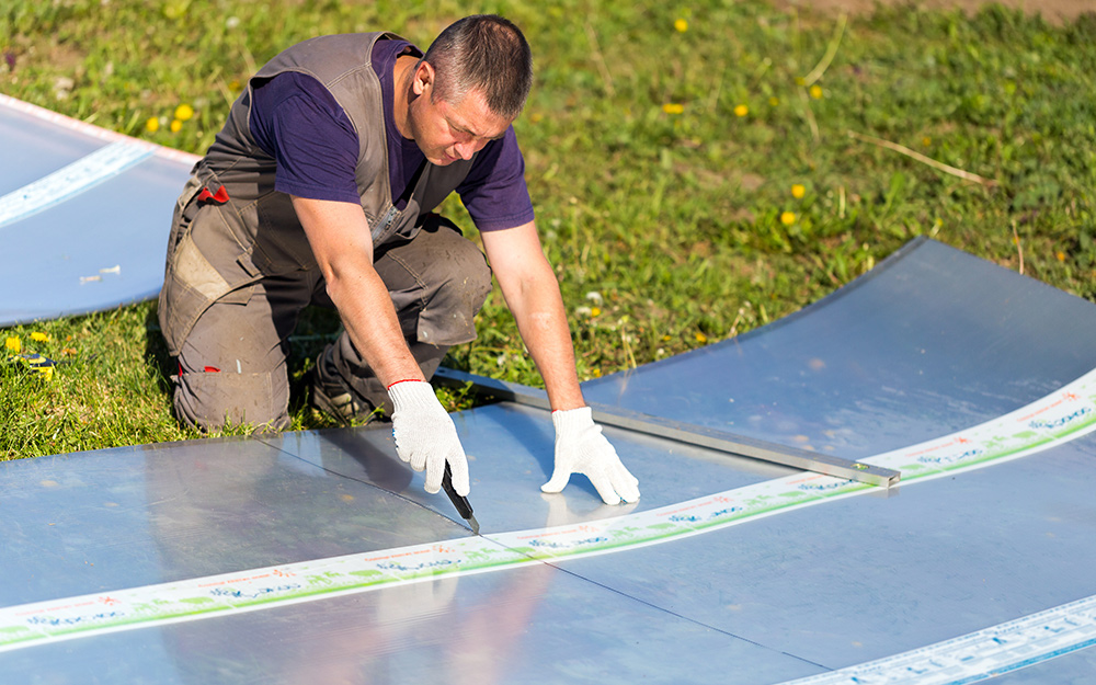 A person cutting a polycarbonate panel with a utility knife.