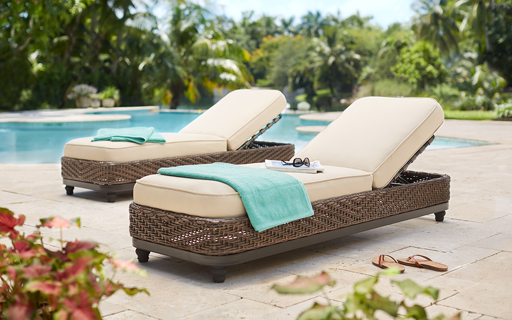 luxury dark brown wicker poolside loungers with neutral cushions