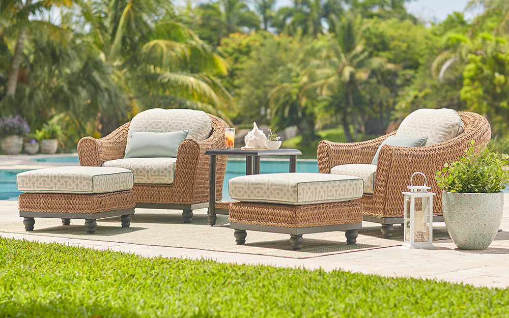 tan brown wicker poolside lounge set with cushions and ottomans