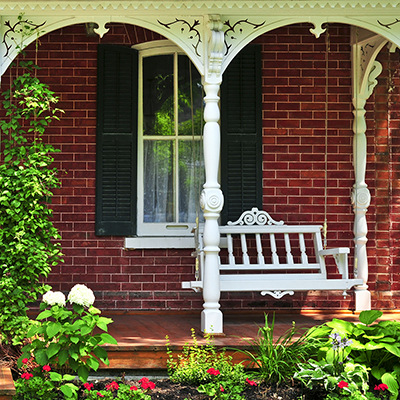 a front porch featuring a white porch swing