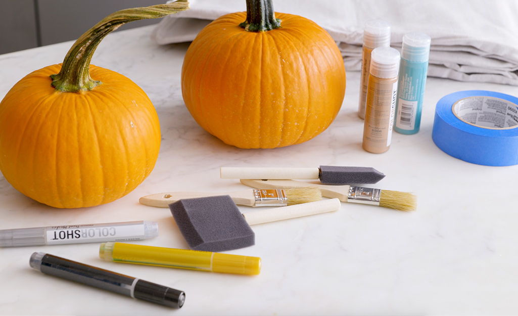 Two pumpkins and various painting supplies.