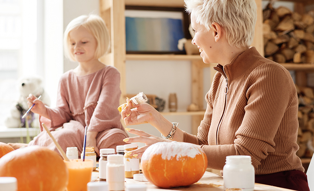 A woman and child painting pumpkins.
