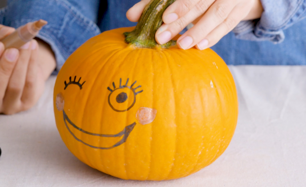 A pumpkin painted with a smiling face.