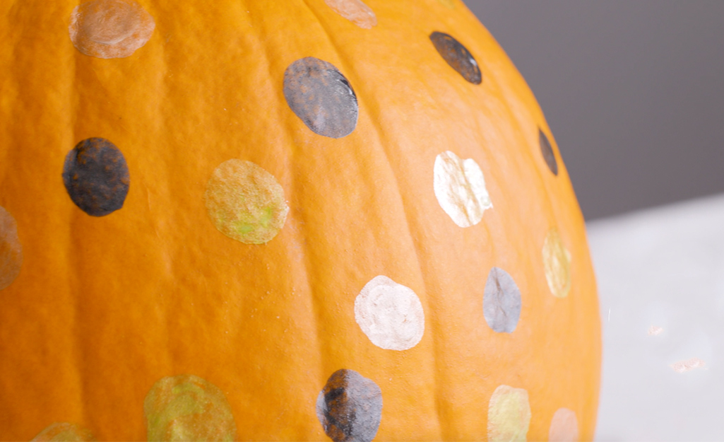 A pumpkin with black, silver, gold and white polka dots.