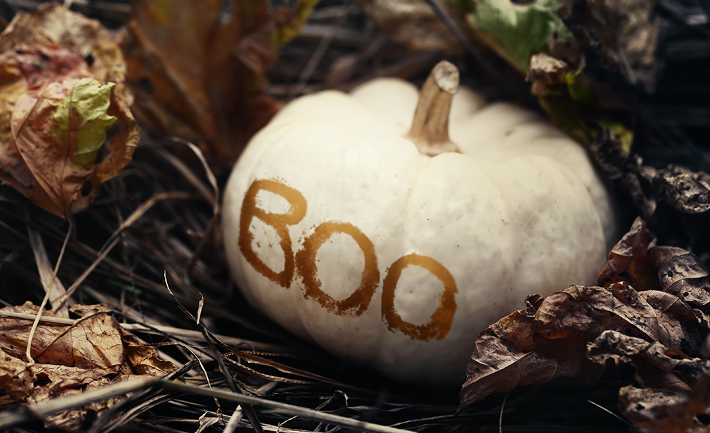 """A pumpkin painted with a white base with the word """"BOO"""" in gold paint."""