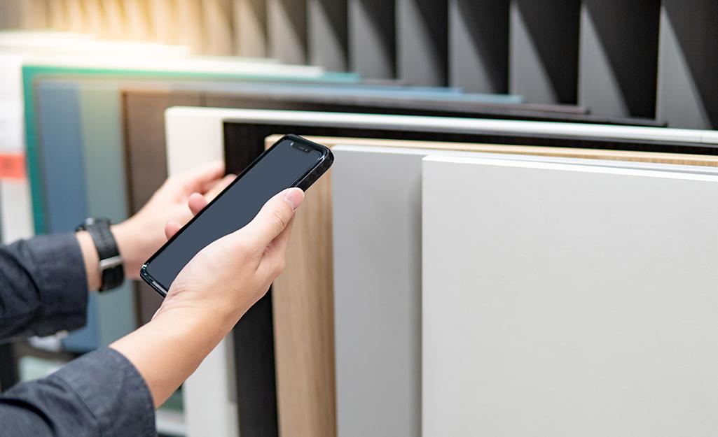 Một người cầm điện thoại thông minh trong khi so sánh các phiến thạch anh khác nhau.