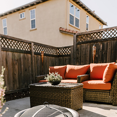 A patio with wicker furniture surrounded by a wood fence.
