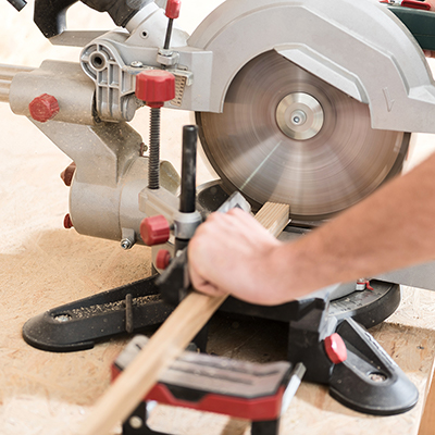 A person uses a radial arm saw to cut a piece of wood.