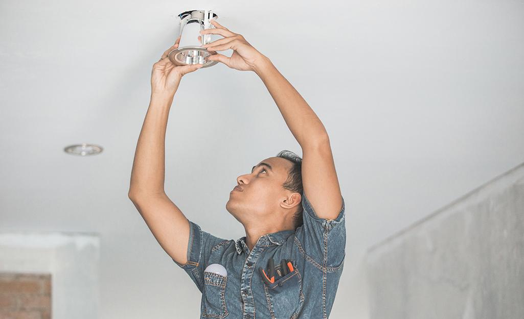 Một người lắp đèn âm trần trên trần nhà.