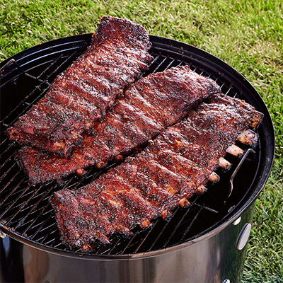 Three racks of St. Louis-style ribs cooking on an outdoor grill.