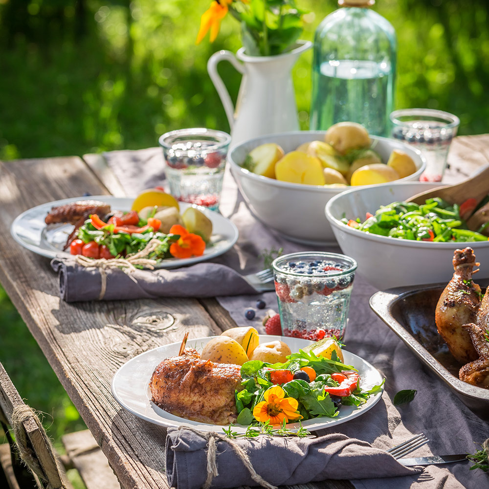 An outdoor table with plates of food