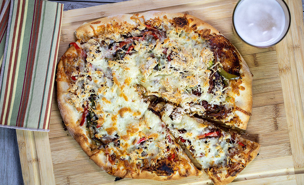 Pizza with grilled peppers on a cutting board