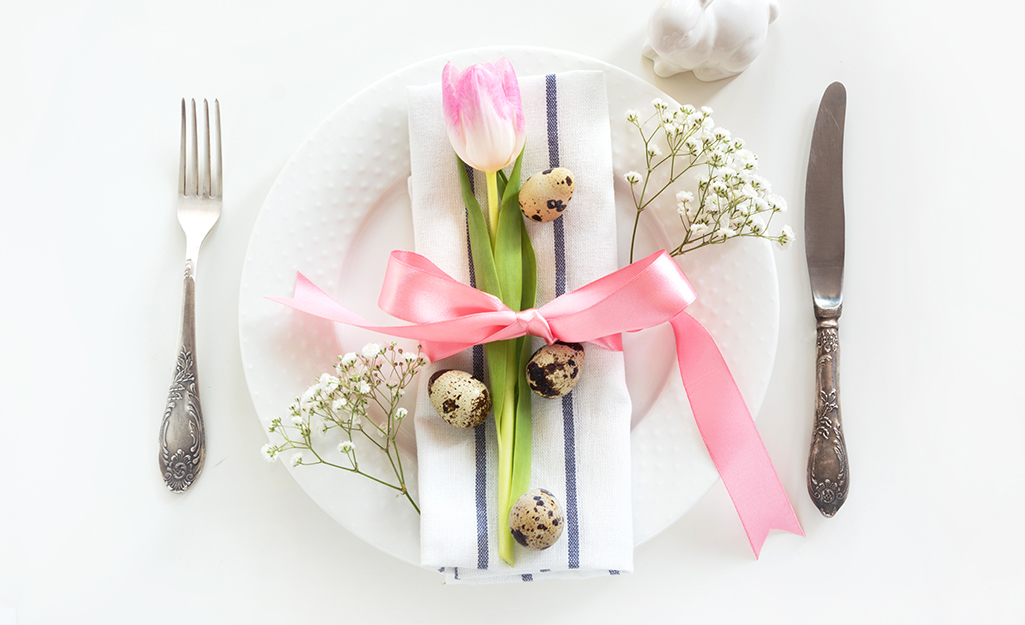 A place setting with a white napkin and pink tulip.