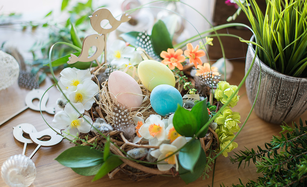 A bird's nest centerpiece with colored eggs, greenery and feathers on a table.