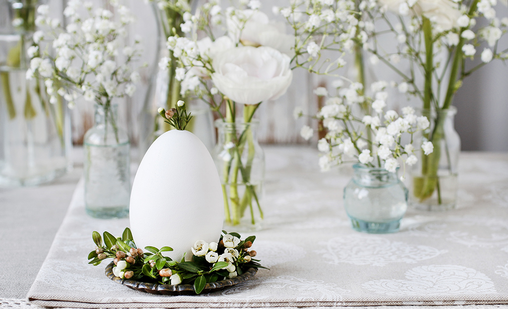 A hallowed out white egg with sprigs of heather in it on a table.