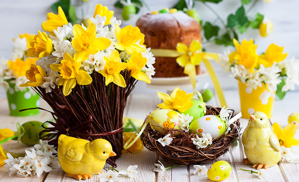 Yellow daffodil arrangements in grapevine vase and basket on a table.
