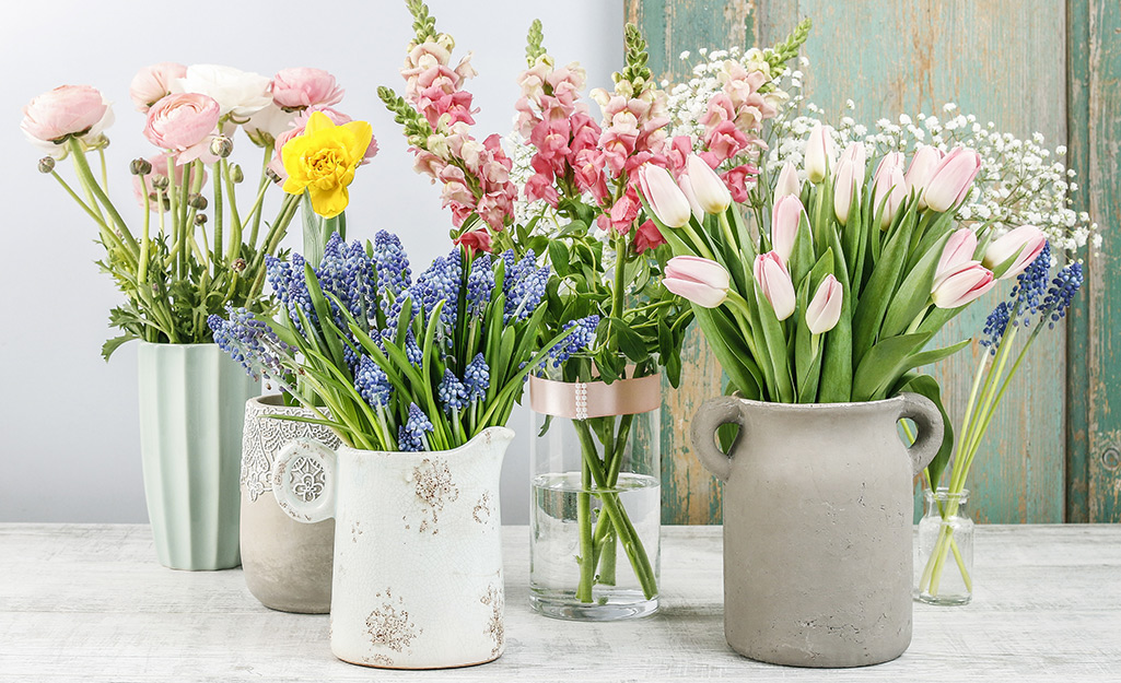 Several containers of spring bulb flowers on a table.