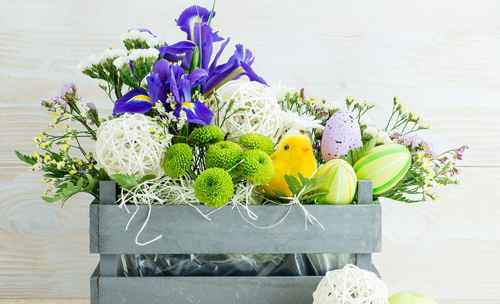 A crate of flowers with faux eggs and a chick.
