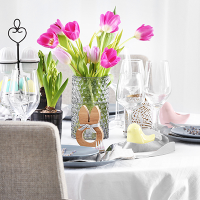 A dining table with a vase of pink tulips.