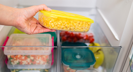 Person placing a container of leftover corn in a refrigerator drawer.
