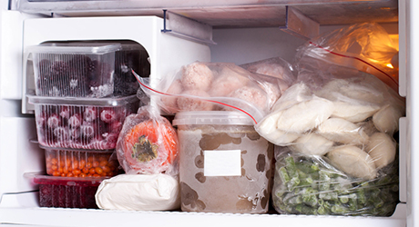 Inside of a freezer compartment with stacked frozen food.
