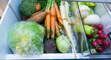 Vegetable compartment of a refrigerator filled with vegetables.