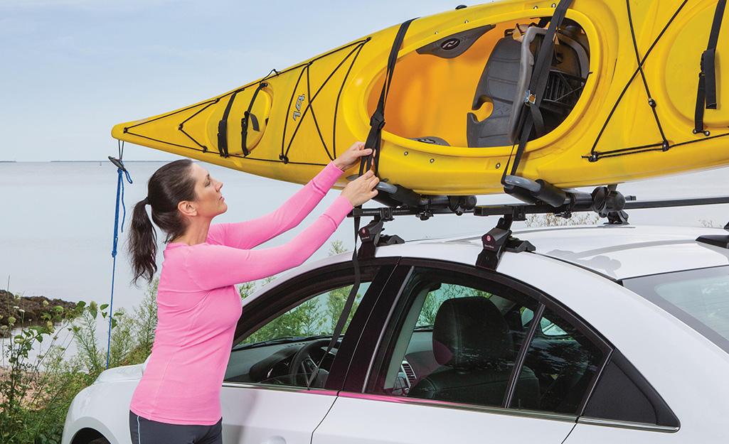 một người phụ nữ đặt một chiếc thuyền kayak trên một chiếc kẹp trên mái nhà