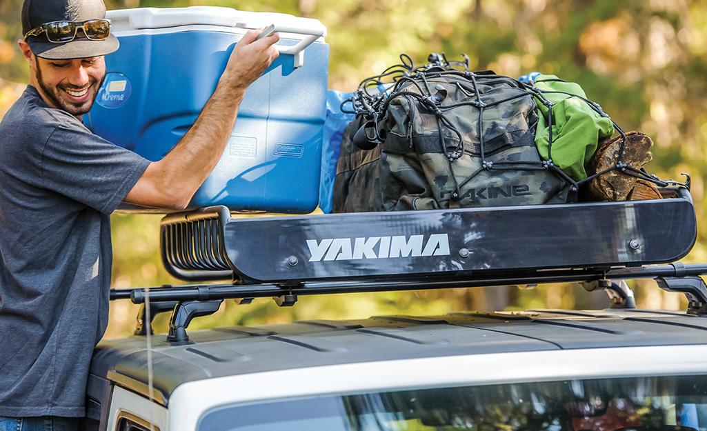 một người đàn ông đang tải một thùng làm mát nước lên giá trên mái nhà