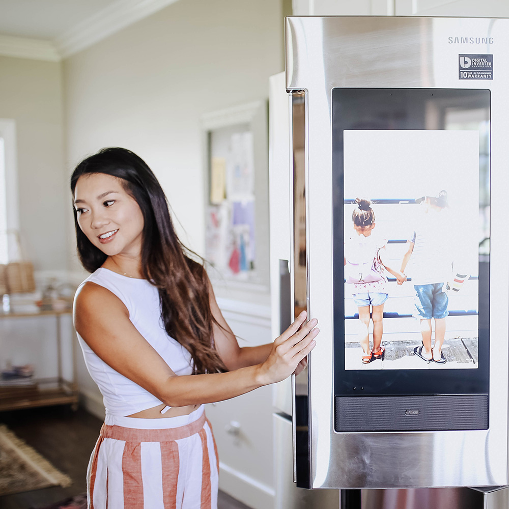 A woman standing in front of a Samsung smart refrigerator with the door open.