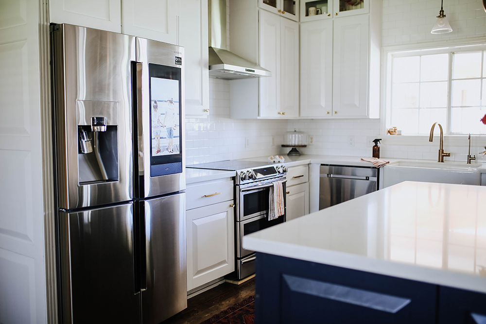 A bright white kitchen with stainless steel Samsung appliances.
