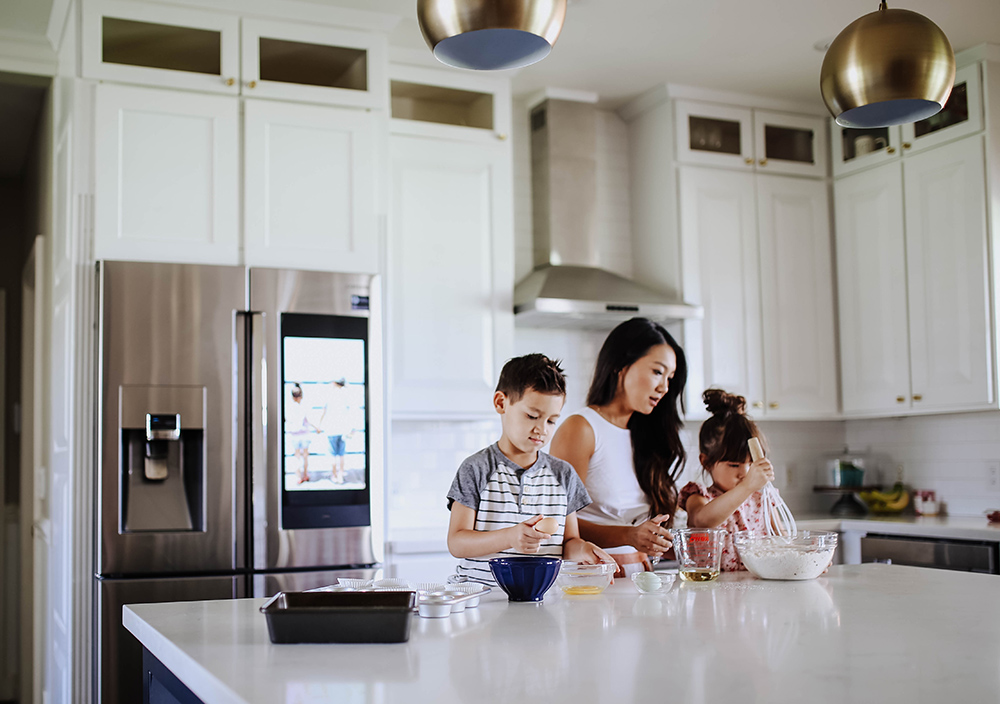 A woman and two children mix ingredients at a kitchen island.