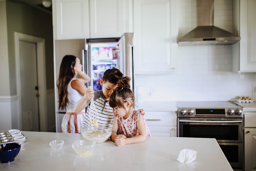 Two children whisk ingredients in a bowl at a kitchen island.