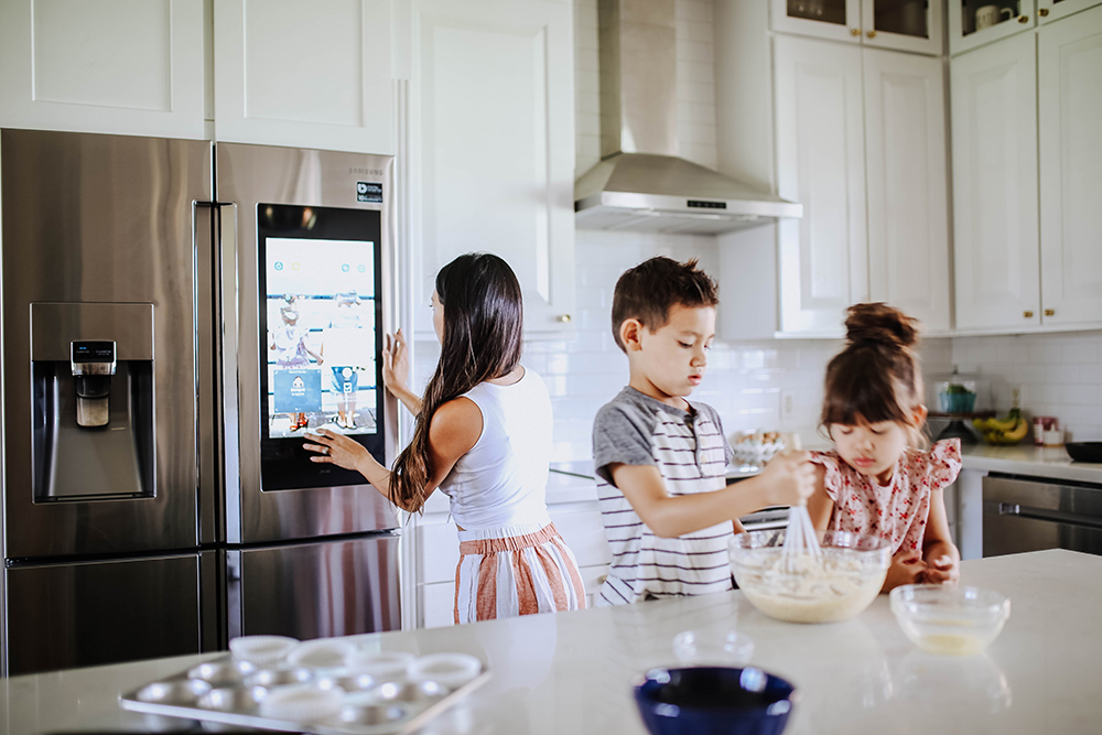 A woman touching the screen on a Samsung smart refrigerator white two children sit at a kitchen island.
