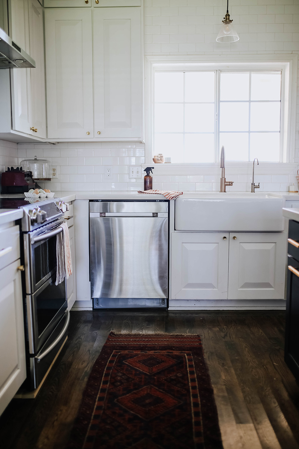 A stainless steel Samsung dishwasher in the corner of a kitchen surrounded by white kitchen cabinets.