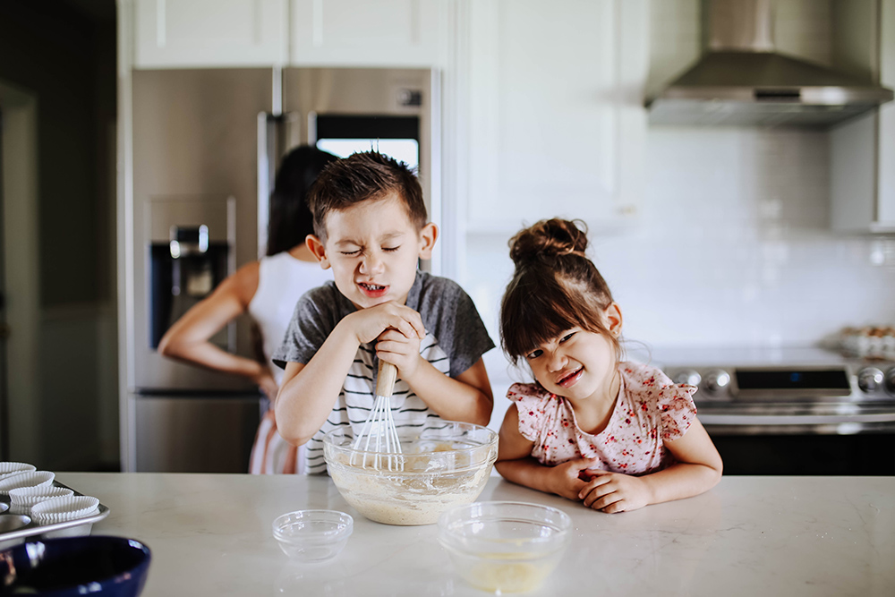 Two children making faces sit at a kitchen island while whisking ingredients in a bowl.