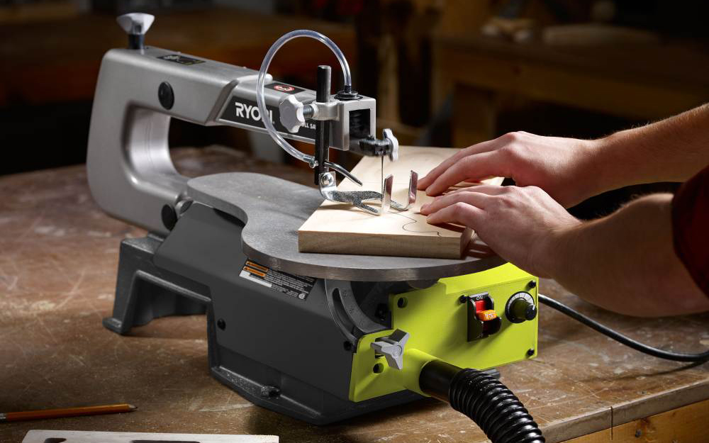 person using a scroll saw to cut a DIY wooden craft
