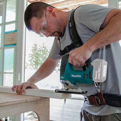 Man using a router to drill through a board.
