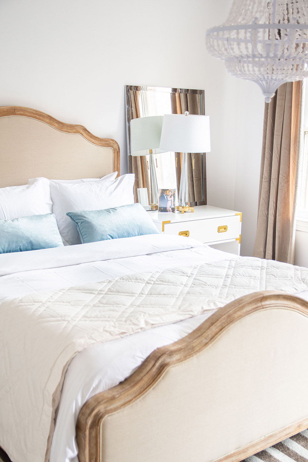 A bedroom scene featuring a bed with ivory bedding, an overhead light fixture and furniture.